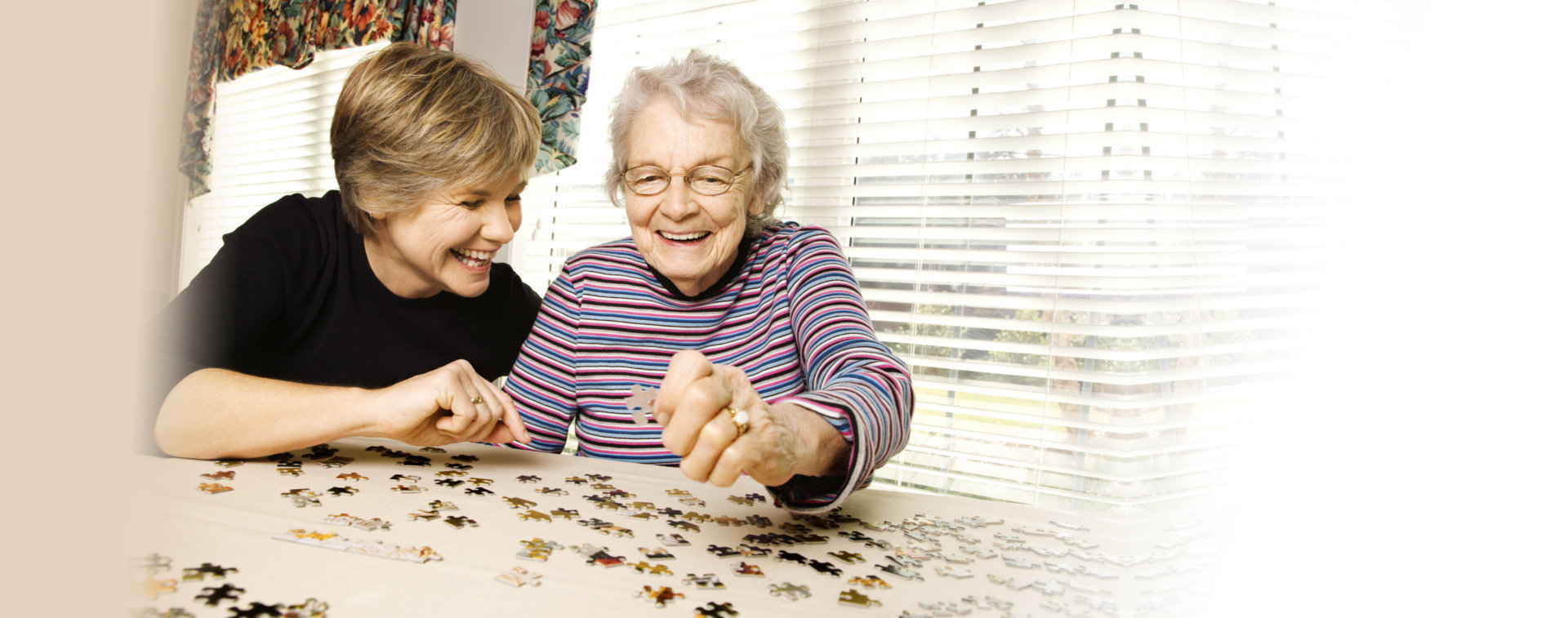caregiver and elderly woman playing jigsaw puzzle