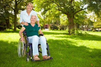 caregiver assisting an elderly in a wheelchair outside